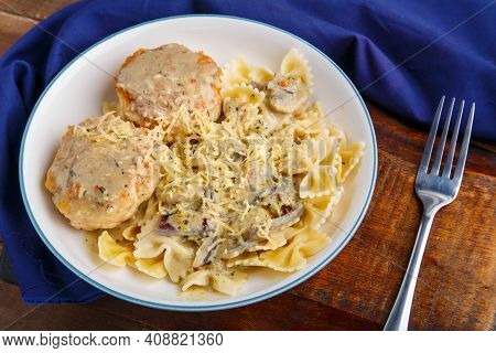 Pasta In A Creamy Sauce With Mushrooms And Chicken Meatballs In A Beige Plate On A Wooden Table On A