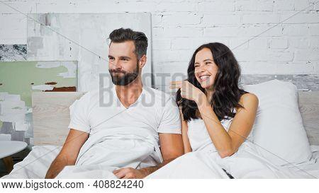 Joyful Brunette Woman Pointing At Discouraged Boyfriend In Bedroom.