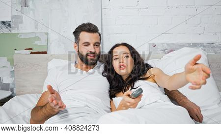 Discouraged Man And Woman Pointing With Hands While Watching Tv In Bedroom.