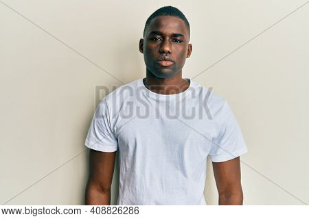 Young african american man wearing casual white t shirt with serious expression on face. simple and natural looking at the camera.