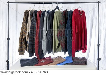 Horizontal Shot Of A Group Of Men's Sweaters Displayed At An Estate Sale Or Garage Sale.