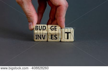 Invest Or Budget Symbol. Businessman Turne Wooden Cubes And Changes The Word 'invest' To 'budget'. B