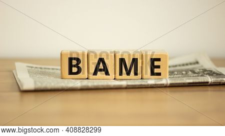 Bame Symbol. Abbreviation Bame, Black, Asian And Minority Ethnic On Wooden Cubes On Newspaper. Beaut
