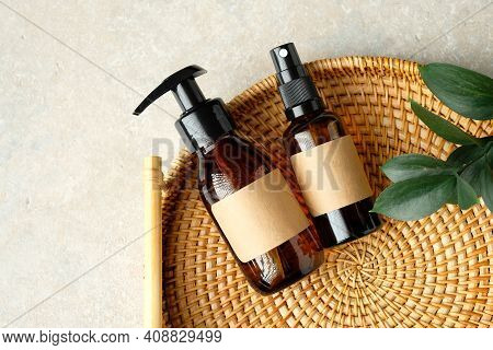 Amber Glass Bottles Of Natural Cosmetics And Green Leaf In Rattan Plate. Spa Organic Bathroom Beauty
