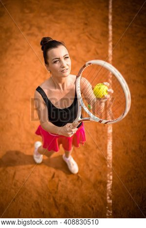 Top view of attractive young woman tennis player serving on a clay tennis court. Interesting POV shot -  sporty girl during tennis training in the club