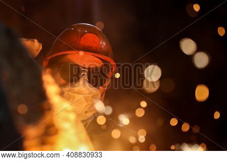 A Steelmaker Pours Pig Iron From A Blast Furnace, Sparks And Splashes Of Hot Metal Fly 1.