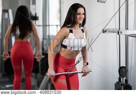Woman Training On A Pulley Machine In The Gym