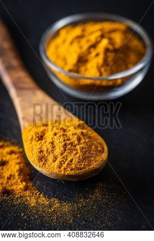 Indian turmeric powder. Turmeric spice. Ground turmeric in wooden spoon on black table.