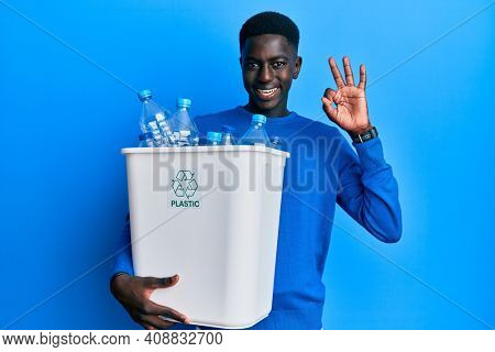 Young african american man holding recycling wastebasket with plastic bottles doing ok sign with fingers, smiling friendly gesturing excellent symbol