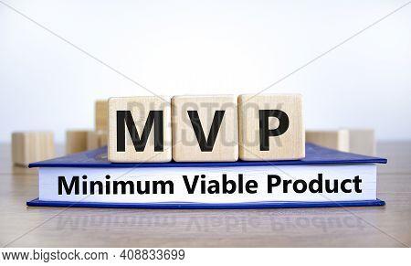 Mvp, Minimum Viable Product Symbol. Wooden Cubes On Book With Words Mvp, Minimum Viable Product. Bea