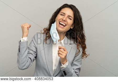 Studio Portrait Of Happy Business Woman Taking Off Mask, Raising Fist, Grey Background. Female Remov