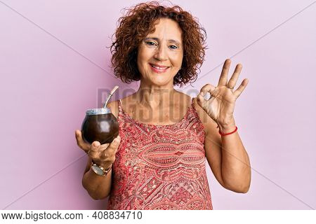 Beautiful middle age mature woman drinking mate infusion doing ok sign with fingers, smiling friendly gesturing excellent symbol