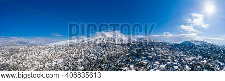 Attica Greece. Penteli Mountain Covered With Snow, Aerial Drone View, Blue Sky Background