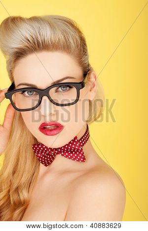 Head and shoulders portrait on yellow of a glamorous retro blonde fashion model wearing only heavy rimmed glasses and a sexy red bowtie