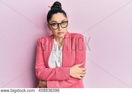 Beautiful middle eastern woman wearing business jacket and glasses shaking and freezing for winter cold with sad and shock expression on face