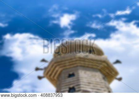 A Mosque Minaret On Blue Cloudy Sky Background. Blurred View