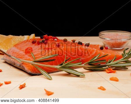 Close-up Of Slice Of Red Fresh Raw Salmon Fillet With Pepper And Spices And Rosemary Next To It. Lie
