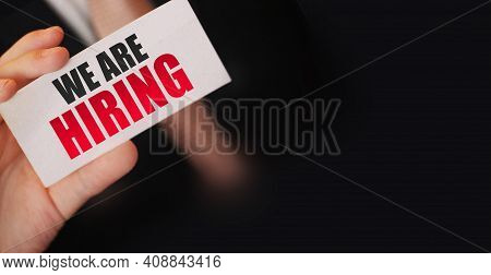 Businessman Holds A Card With The Text We Are Hiring. Business Concept.