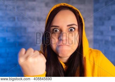 Portrait Of Dissatisfied Young Woman Showing Fist. Close Up Of Distraught Female In Yellow Hood Show