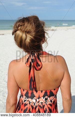 Rear View Of A Beautiful Mature Woman Standing On The Beach Wearing A Summer Dress