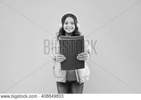 Hooked On Books. Happy Child Hold Books Pink Background. Small Bookworm Wear Headphones. Listening T