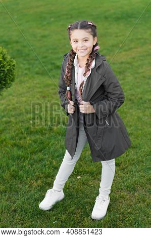 Fashionable Coat. Girl Cute Face Braided Hair Posing Coat In Spring Park. Clothing For Spring Walks.