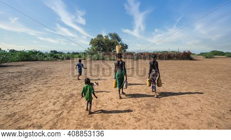 Omorate, Ethiopia - September 2017: Unidentified Woman From Dassanech Tribe Carrying Water To Her Vi
