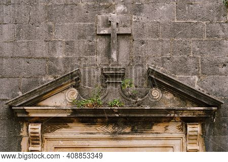 Gray Wall With A Cross Carved Into The Stone In The Style Of A Bas-relief, Above The Entrance To The