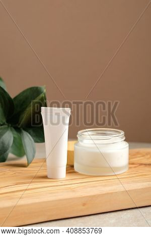 Set Of White Cosmetic Lotion Tube And Jar Of Moisturizer Cream On Wooden Board With Green Leaf. Natu