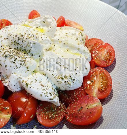 Small Tomatoes, Sliced And Placed On A Plate, Seasoned, Sprinkled With Dried Oregano, Chopped Burrat