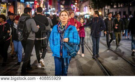 Istanbul, Turkey - November 2019: Woman Walking Alone Among Crowd Of People In Taksim Square Istikla