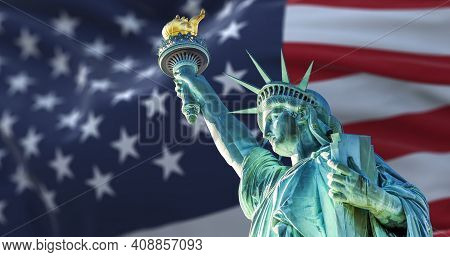 The Statue Of Liberty With The Blurry American Flag Waving In The Background. Democracy And Freedom