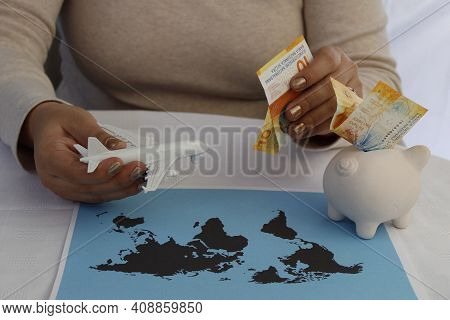 Hands Of A Woman Holding Swiss Money And Plastic Airplane With A Piggy Bank And A World Map On The T