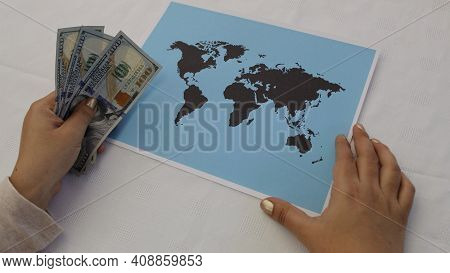 Hands Of A Woman Holding American Dollar Money And A World Map On The Table