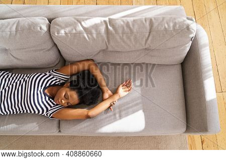 African American Young Woman Wear Stripped T-shirt Sleeping On Couch With Arms Up At Home, Closing E