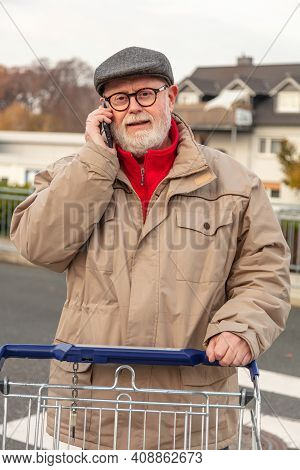 Senior With Winter Cloth Using Cell Phone While He Is Pushing Is Shopping Cart On Parking Area