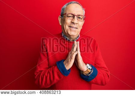Handsome senior man with grey hair wearing casual clothes and glasses praying with hands together asking for forgiveness smiling confident.