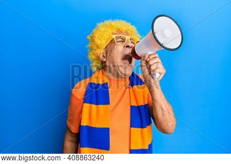 Senior hispanic hooligan man wearing crazy look with glasses and wig supporting football team screaming through megaphone