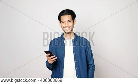 Asian Man Holding Mobile Phone Smiling And Looking At Camera While Standing Isolated On Grey Backgro