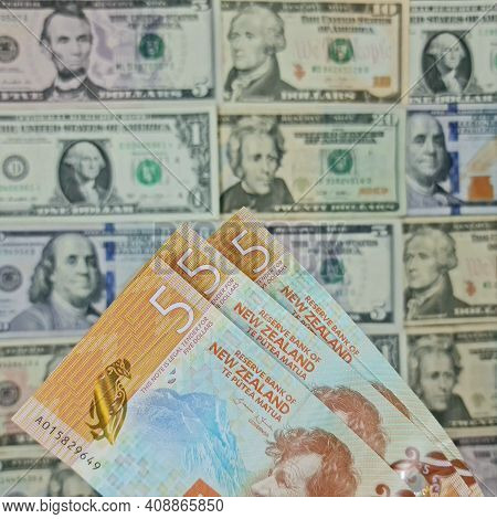 Approach To New Zealand Banknotes And Background With American Dollar Bills