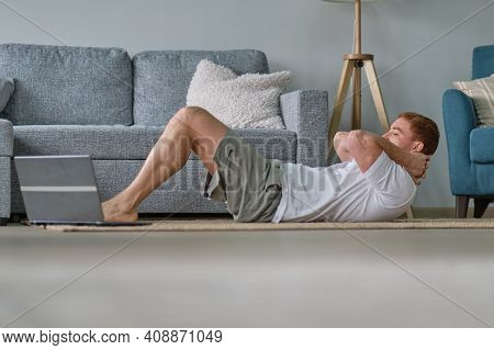 Redhead Man In White T-shirt Works Out In The Living Room. Man Doing Sports On A Mat Watching Videos