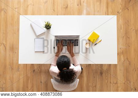 Overhead View Of Mixed-race Ethnic Woman Or Female Freelancer With Curly Hair Sitting At The White T