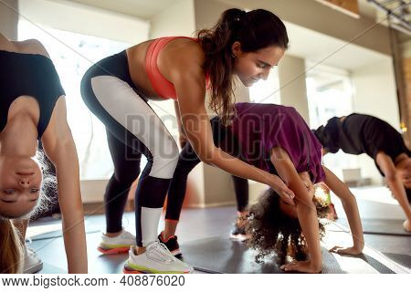 Portrait Of Female Trainer Helping Girl While Kids Are Practising Yoga By Bending Backwards On Mats