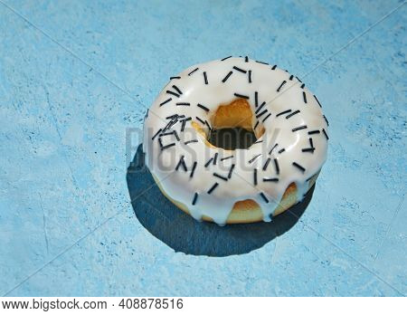 Donut With White Frosting And Sprinkles On Blue Background