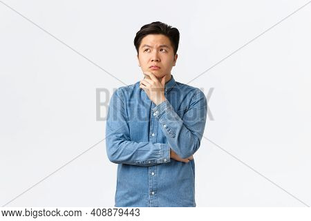 Thoughtful Complicated Asian Man In Shirt, Touching Chin And Looking Upper Left Corner, Thinking, Ma