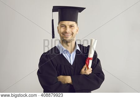 Studio Portrait Of Happy University Graduate Holding His Diploma And Smiling At Camera