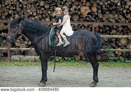 Little Girls Ride On Horse On Summer Day. Equine Therapy, Recreation Concept. Children Smile In Ride