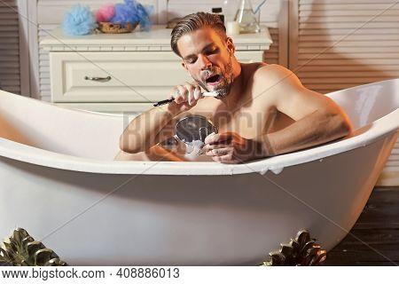 Gay In Bath Tub. Hygiene Routine, Bearded Man Shave Beard Hair In Bathtub