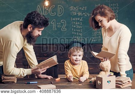 Family Cares About Education Of Their Son. Father And Mother Reading Books, Teaching Their Son, Chal
