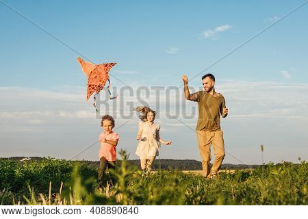 Young Happy Family With Little Boy Run In Field And Flying A Kite.